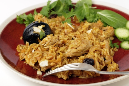 An authentic Saudi chicken kabsa (known in Qatar as majbous), garnished with raisins and toasted almond flakes, on a serving bowl. Kabsa is a national staple for Saudi Arabia and the Arab Gulf States. photo