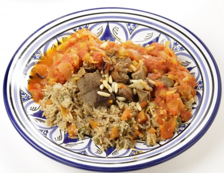 arabian food: A traditional Saudi Arabian or Gulf Arab meat kabsa meal, of rice, onion, carrots, capsicum, spices, and beef, served with a homemade tomato sauce topping. This originates from Yemen and is known as majbus or machboos in some countries, it is being served