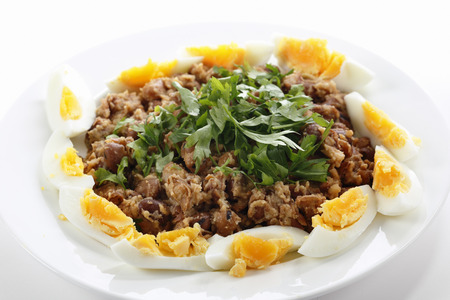 Egyptian foul - or ful - medames on a plate garneshed with slices of hard-boiled egg and flat-leaf parsley. Foulm made from fava beans, lemon juice, olive oil, cumin powder, cayenne salt and black pepper is probably Egypts most famous food.