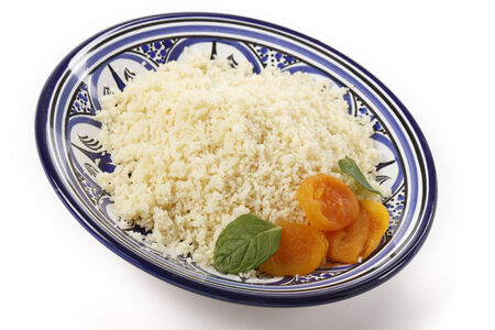 couscous: Plain couscous on a Tunisian handmade and hand-painted plate garnished with dried apricots and mint leaves