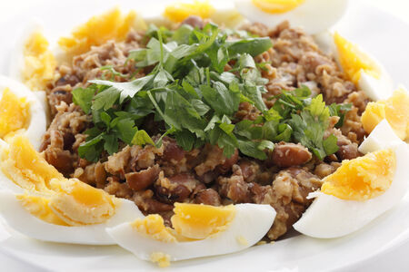 Egyptian foul - or ful - medames on a plate garneshed with slices of hard-boiled egg and flat-leaf parsley. Foulm made from fava beans, lemon juice, olive oil, cumin powder, cayenne salt and black pepper is probably Egypt's most famous food. photo