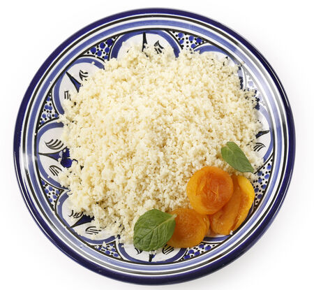 couscous: Plain couscous on a Tunisian handmade and hand-painted plate garnished with dried apricots and mint leaves, viewd from above Stock Photo