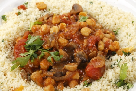 couscous: Moroccan style chickpeas and mushrooms in tomato sauce, served with couscous mixed with parsley and apricots, closeup view Stock Photo