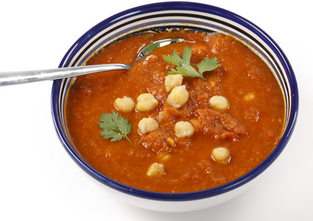 Spicy tomato and chickpea soup in a traditional Tunisian bowl with a spoon, garnished with parsley. photo