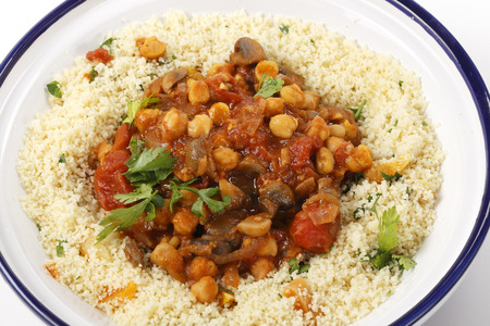 quartered: Chickpeas or garbanzo beans and quartered button mushrooms cooked in a spicy tomato and onion sauce and served with couscous mixed with parsley and refreshed dried apricots, Moroccan style, served in a tagine bowl Stock Photo