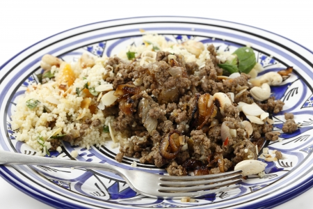 spiced: Minced beef cooked with onion and spices, served with couscous and garnished with toasted nuts and caramelised onion in the North African, Moroccan, style