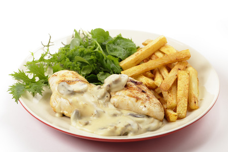 Grilled chicken breasts topped with a creamy mushroom sauce with french fried potato chips and a garden fresh green salad photo