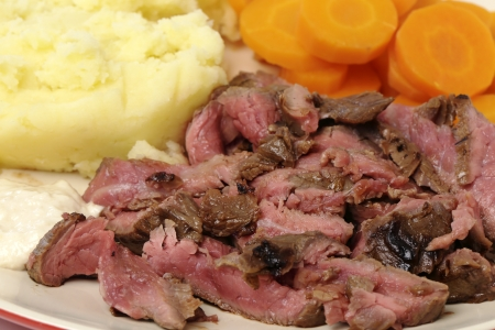 thinly: London broil marinaded flank of beef steak grilled and sliced thinly, then served with mashed potato, boiled sliced carrots and horseradish sauce, close-up side view Stock Photo