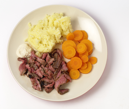 London broil marinaded flank of beef steak grilled and sliced thinly, then served with mashed potato, boiled sliced carrots and horseradish sauce, from above