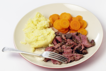 London broil marinaded flank of beef steak grilled and sliced thinly, then served with mashed potato, boiled sliced carrots and horseradish sauce