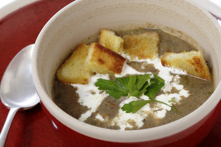 Homemade cream of mushroom soup in a bowl with croutons and parsley photo