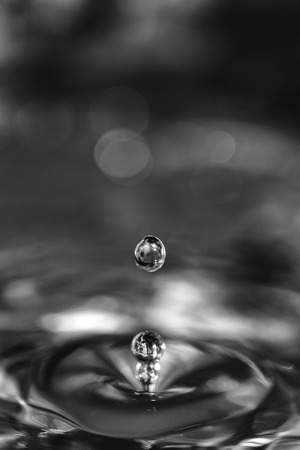 spread around: Pearl-like water-drops rebound from the surface of a pool of water, with one looking almost like the stamen of a flower as the ripples spread around it like petals