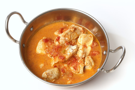 Basic fish curry, in a spicy tomato and coconut milk sauce, in a kadai (karahi or wok) serving bowl photo