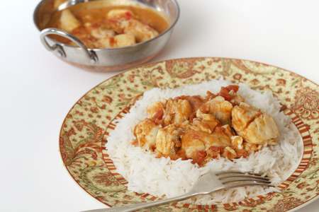 indian cookery: Basic fish curry, in a spicy tomato and coconut milk sauce, served on a bed of basmati rice, with a kadai (or karahi or wok) serving bowl.