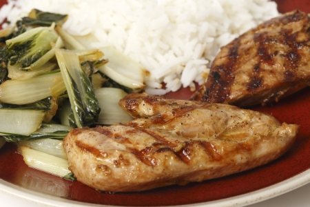 Soy sauce marinaded chicken breasts served with sauteed pak choi and Thai Jasmine rice, seen close-up photo