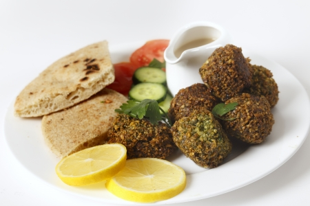 Homemade falafels  herbed and spicy chickpea balls  on a plate with Egyptian flat bread, lemon slices, tomato, cucumber and a tahina sauce