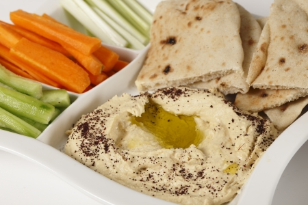 humus: A dip tray with hummus, bread, carrot sticks, celery and cucumber.