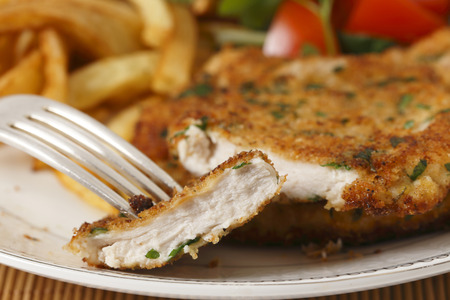chicken meat: A piece of homemade breaded chicken schnitzel or escalope on a fork with french fries and a tomato and green salad behind Stock Photo