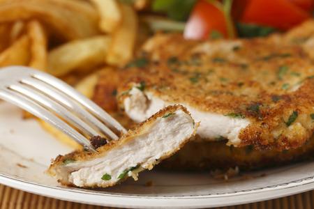 Een stuk van de zelfgemaakte gepaneerde kip schnitzel of schnitzel op een bord met frietjes en een tomaat en groene salade achter