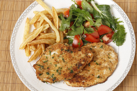 breaded chicken schnitzels or escalopes with french fries and a tomato and green salad photo