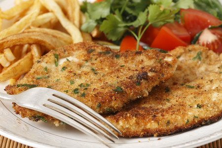 breaded homemade chicken schnitzels or escalopes with french fries and a tomato and green salad photo