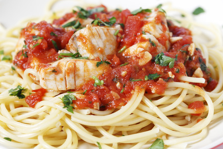 flaked: Spaghetti allarrabbiata with fish, garnished with parsley, seen closeup form the side. The sauce is made from tomato, garlic, olive oil and flaked chillis. Stock Photo
