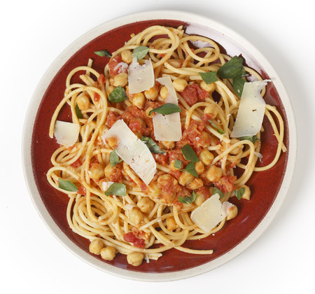 red gram: Spaghetti with a chickpea, tomato and chilli flakes sauce, garnished with fresh torn basil leaves and flakes of parmesan.  Stock Photo