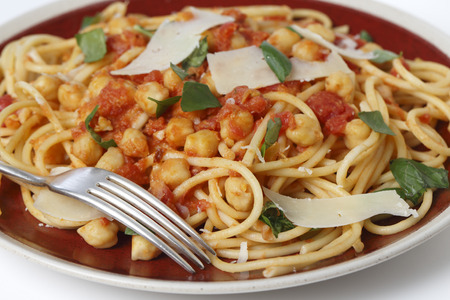 simple meal: Spaghetti with a chickpea, tomato and chilli flakes sauce, garnished with fresh torn basil leaves and flakes of parmesan.