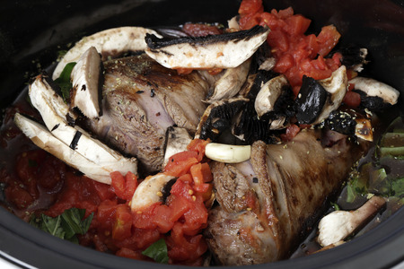 slow cooker: Two lamb shanks, lightly browned ready for cooking in a slow cooker, or crockpot, with mushrooms, tomatoes, basil, red wine  and stock