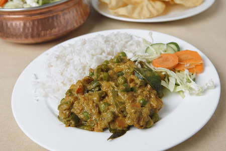 vegs: Vegetable korma curry with a raw vegetable salad, white rice and poppadums. Stock Photo
