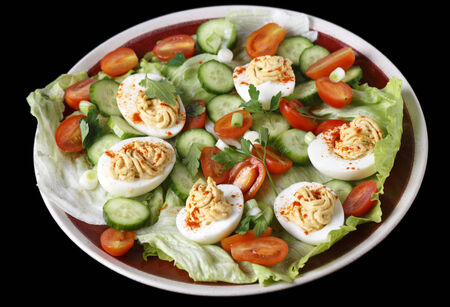 Closeup view of a salad of deviled eggs served with lettuce, miniature tomatoes, sliced cucumber and chopped green onions or scallions photo