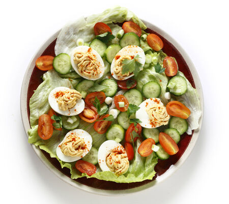 deviled eggs: Homemade deviled eggs served on a salad of minature tomatoes, lettuce, sliced cucumber and chopped green onion scallions.