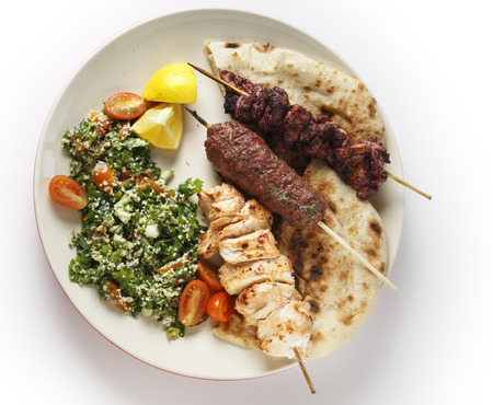 kebab: Various barbecued kebabs - kofta, chicken tawook and sumac chicken - with tabouleh and pitta bread; an Arab or Lebanese-style feast, seen from above