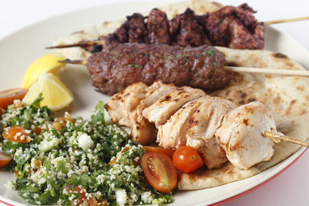 Various barbecued kebabs - kofta, chicken tawook and sumac chicken - with tabouleh and pitta bread; an Arab or Lebanese-style feast. Stock Photo