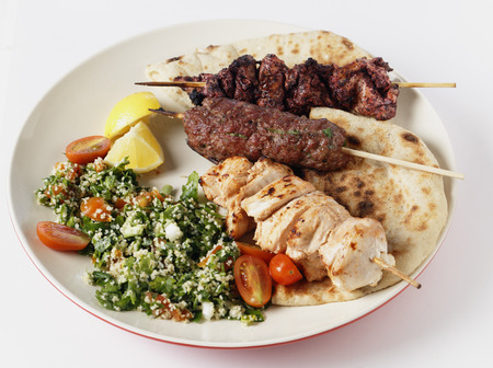 barbecued: Various barbecued kebabs - kofta, chicken tawook and sumac chicken - with tabouleh and pitta bread; an Arab or Lebanese-style feast. Stock Photo