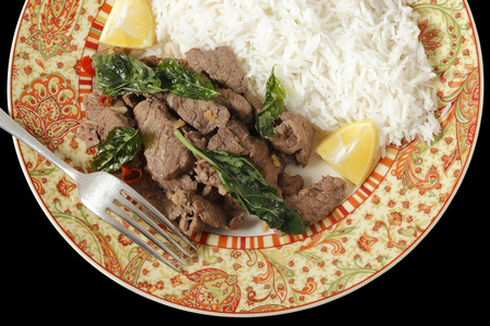 stir fried: Chilli beef with crispy fried basil leaves, served with white basmati rice and lemon wedges, seen from above over black Stock Photo