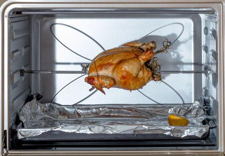 pollo rostizado: Pollo fresco, atado, relleno de hierbas y cocinar en un asador en un horno doméstico Foto de archivo