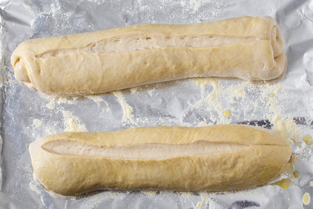 cornflour: Two rolled up batons of Italian-style bread dough, glazed with egg-wash, slashed and left to rise on a baking sheet