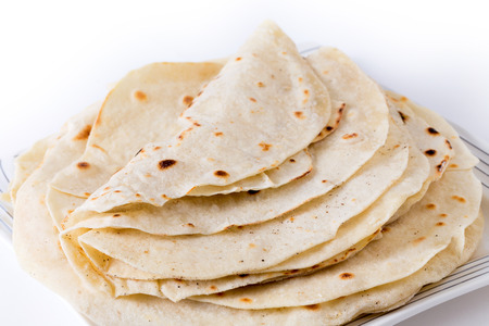 taco tortilla: A pile of fresh homemade wheat tortillas on a plate.