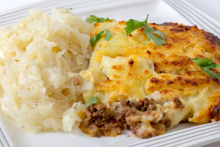 british food: Shepherds pie - or cottage pie - meal served with cabbage and garnished with parsley.