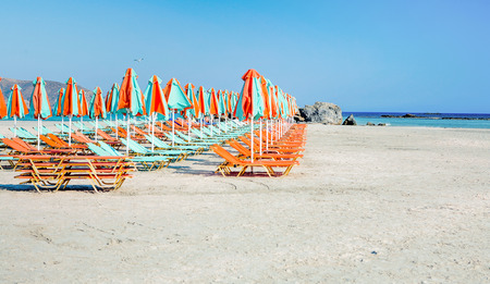 Sun loungers on a sandy beach waiting for tourists to arrive, shot on Elafonissos, Crete, Greece photo