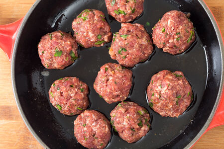 topdown: Top-down view on home-made raw meatballs in a frying pan ready to cook. Stock Photo