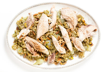ground nuts: Lebanese cinnamon dusted chicken served on a bed of freekeh fire-dried green wheat with a garnish of toasted nuts, seen from above.