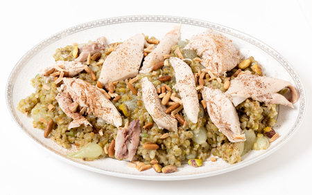 Lebanese cinnamon dusted chicken served on a bed of freekeh fire-dried green wheat with a garnish of toasted nuts. The grain, also spelt frikeh, has a very low glycemic index and is high in fibre, protein and minerals, making it a good diet or diabetic op 版權商用圖片 - 33389446