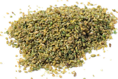 immature: A heap of frikeh or freekeh grains on a white background. The cereal is made from immature, green wheat which is fire-roasted to make a healthy, low-glycemic-index food which is high in protein and minerals, making it an option for a diabetic diet. Boiled