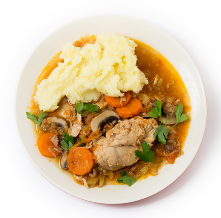 braised mushrooms: Top view of a  meal of chicken cacciatore, braised chicken cooked with tomato, celery, carrot, onion, mushrooms and stock and served with mashed potatoes.