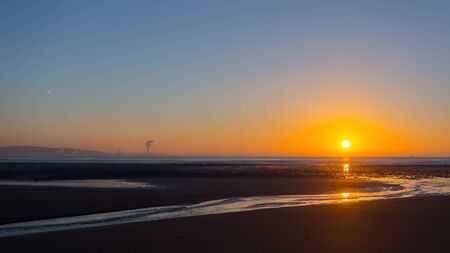 Sunrise over Swansea beach, South Wales, on a clear winter morning, with the industrial emissions from Port Talbot visible across the bay and a plane