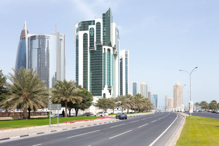 public works: DOHA, Qatar - February 11, 2015: The Corniche road with the Public Works Authority, Salaam Tower and Doha Bank tower.