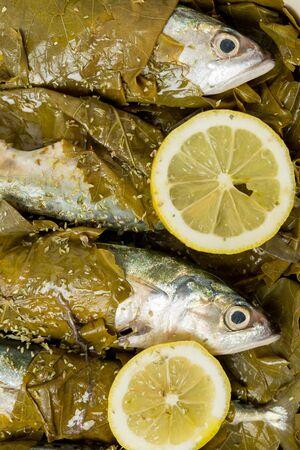 hojas parra: Caballa listo para su cocci�n en hojas de parra, con aceite de oliva, lim�n y or�gano, un plato tradicional griego con peque�a caballa o sardinas