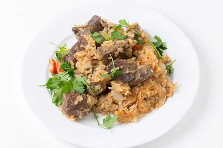 higado de pollo: sofrito trozos corderos hepáticos horneados en la parte superior de un pilaf de arroz, cebolla, tomate, pimiento y pasas de Corinto en un caldo de pollo, en una pequeña placa con guarnición de perejil italiano. Esta es una receta excepcional.